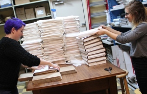 Booksellers Steph and Ryllis show off their lightning-fast box-folding talents while packing up copies of signed books to send to members of the Parnassus Books First Editions Club.